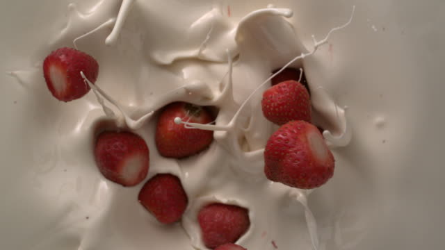 vidéos et rushes de whirlpool with strawberry falling down on white creamy liquid tabletop in slow motion - fraise