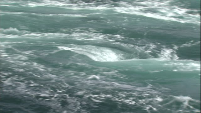 Whirlpools form in the wild seawater of the Naruto Strait in Japan.