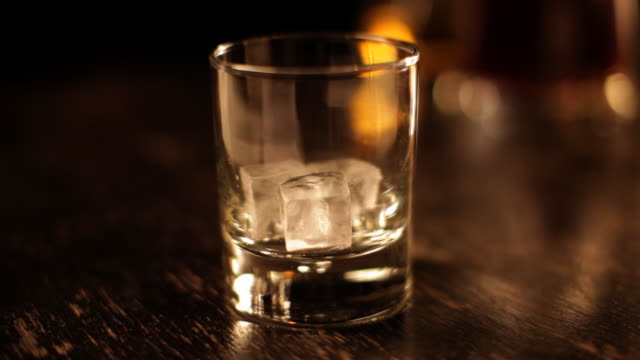 Whiskey glass filled with ice and drink, close-up