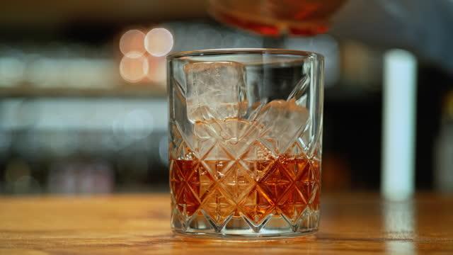vidéos et rushes de whiskey slo mo ds versé dans un verre à pierres - bar