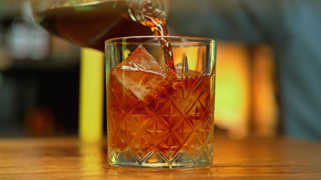 slo mo ds whiskey poured into a rocks glass with ice cubes - dolly shot stock videos & royalty-free footage