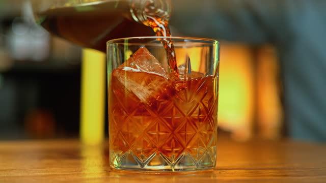 vídeos de stock e filmes b-roll de slo mo ds whiskey poured into a rocks glass with ice cubes - plano charriot