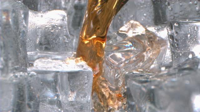 whiskey splash on ice inside a glass in high speed - アイスティー点の映像素材/bロール