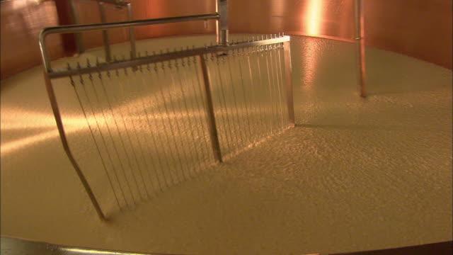 vídeos y material grabado en eventos de stock de whisks mix cheese in a copper vat. - queso