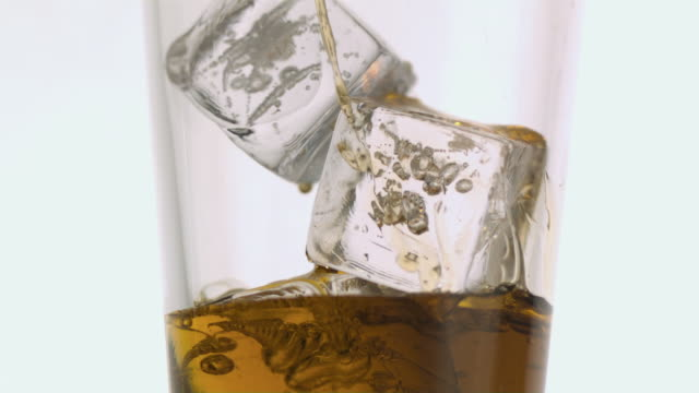 cu slo mo whisky being poured into glass over ice / new jersey, usa - scotch whiskey stock videos and b-roll footage