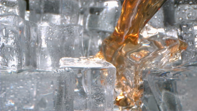 whisky is pouring onto ice cubes in a glass in slow motion camera dollying out - ice cube stock videos & royalty-free footage