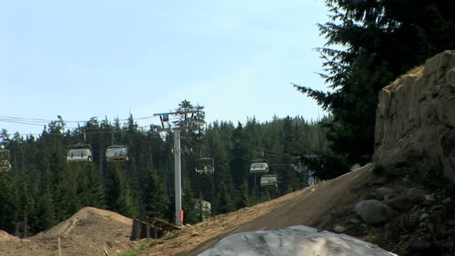 WS Whistler Mountain chairlift used as mountain bike park in summer, person jumping on bike in foreground, Whistler, British Columbia, Canada