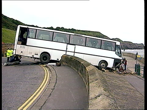 coach crash itn england yorks whitby ext coach crashed thru sea wall police officers around coach - whitby north yorkshire england stock videos & royalty-free footage