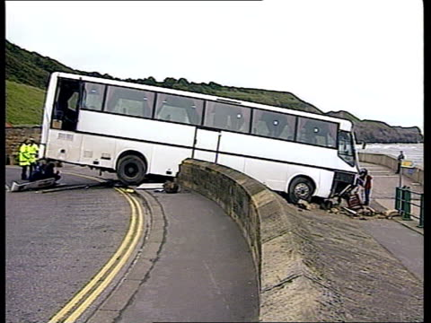 coach crash itn england yorks whitby ext coach crashed thru sea wall wreckage on grass tilt up police at scene of crash bv crashed coach - whitby north yorkshire england stock videos & royalty-free footage
