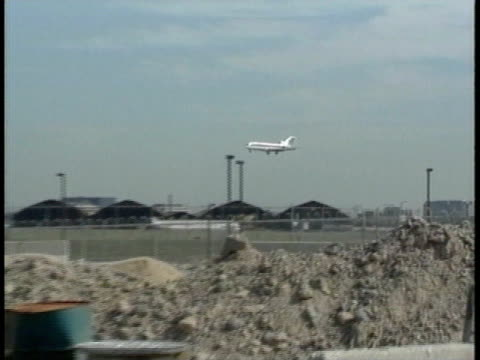 white airplane descending, coming in for landing, at airport, construction equipment, rubble, & unidentifiable crewmen welding, working on pipes fg.... - passenger 個影片檔及 b 捲影像