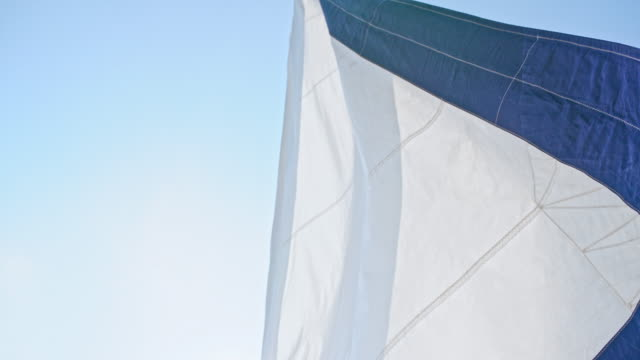 vídeos de stock e filmes b-roll de 4k white and blue sailboat sail blowing in wind against sunny blue sky, real time - vela desporto aquático