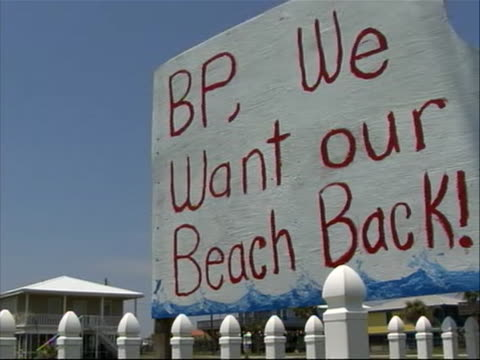 """white and red painted sign reading """"bp we want our beach back"""" atop white picket fence with house seen in the background - louisiana stock videos & royalty-free footage"""