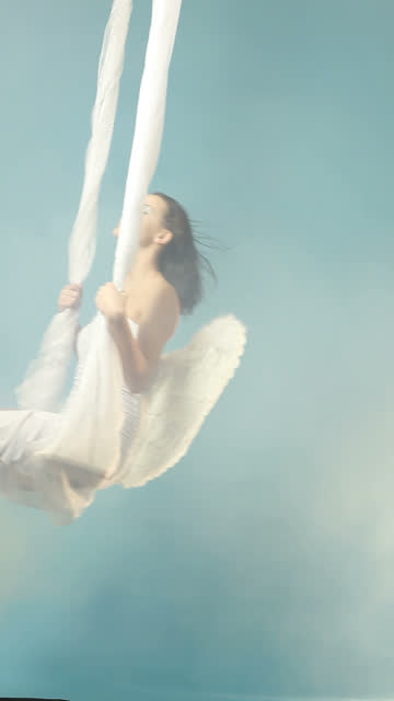 White Angel swaying on blue cloudy sky