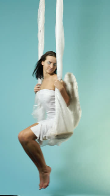 white angel swaying on blue cloudy sky - levitation stock videos & royalty-free footage