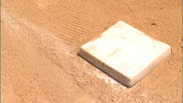 White base on baseball field w/ dirt Sports bases first base second base third base not home plate baseman infield baserunner stealing stolen base