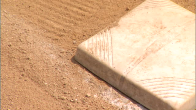 White base on baseball field w/ dirt Sports bases first base second base third base not home plate baseman infield baserunner stealing hit walk...