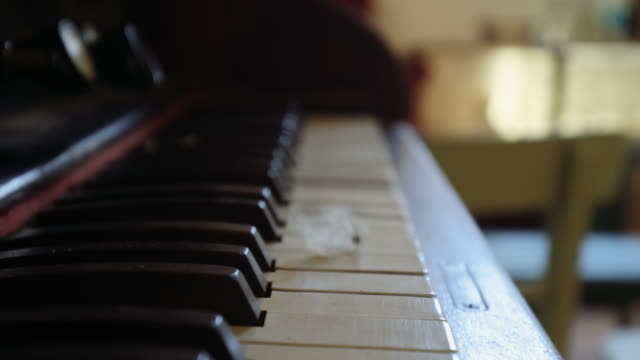 4k white bird feather falls down slowly over the keys of an old piano - falls church stock videos & royalty-free footage