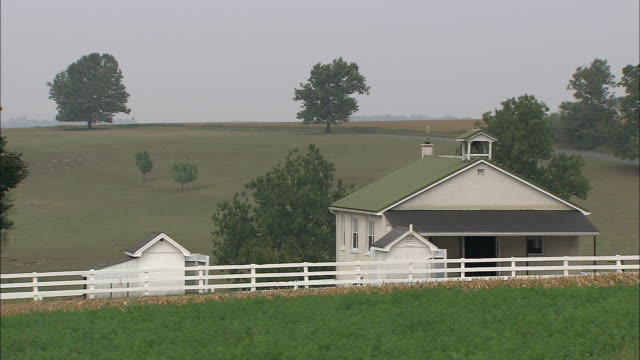 A white board fence runs past an Amish school building near Lancaster County farmland.