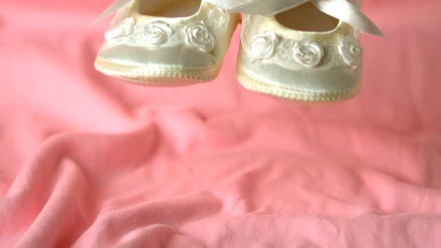 white booties falling on pink blanket - 赤ちゃんの靴点の映像素材/bロール