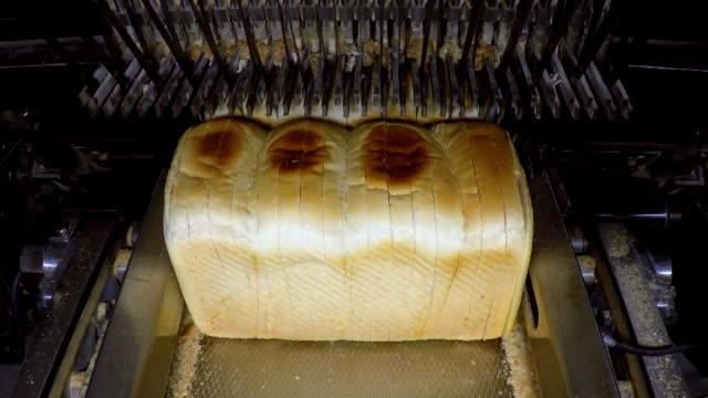 White bread loaves passing through a slicer in a bread factory