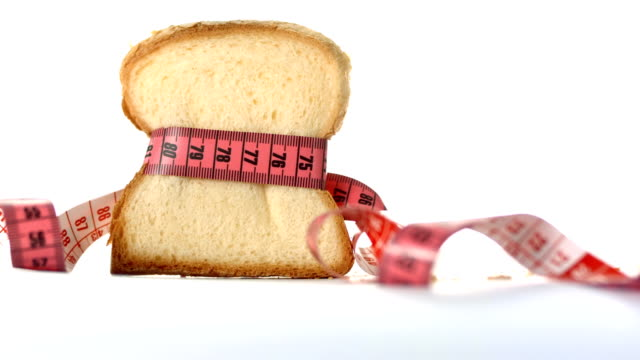 hd: white bread wrapped in measuring tape - white bread stock videos and b-roll footage