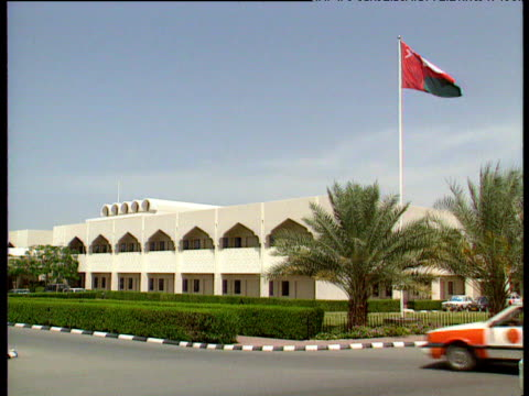 white building with neat green hedges palm trees and oman flag taxi moves along street past building - oman flag stock videos and b-roll footage