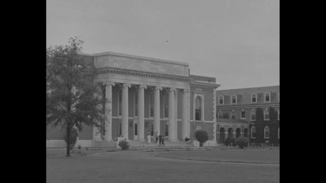 White building with porch columns seen through trees / Lilly Library / young women quickly walking / East Campus Theater / structure with attached...