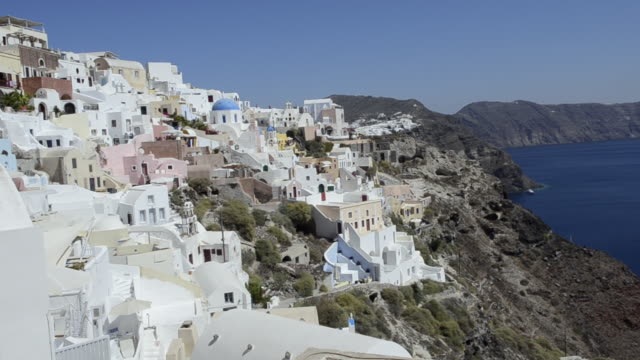 ws pan white buildings at high up on cliffs / fira, santorini, greece - oia santorini stock videos & royalty-free footage