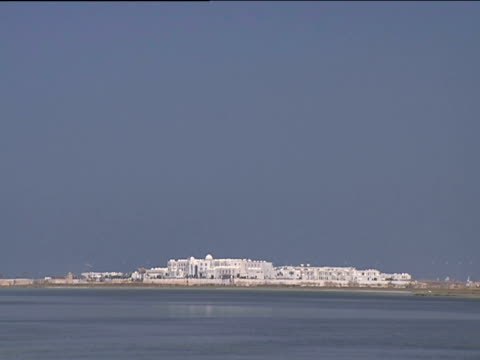 White buildings nestled on coast sea in foreground huge expanse of blue sky above Tunisia