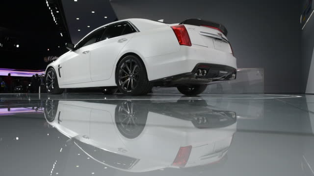 stockvideo's en b-roll-footage met a white cadillac ct5 sits on a rotating stage at the 2015 detroit auto show in detroit michigan close up shots of the cadillac medallion and logo on... - bumper