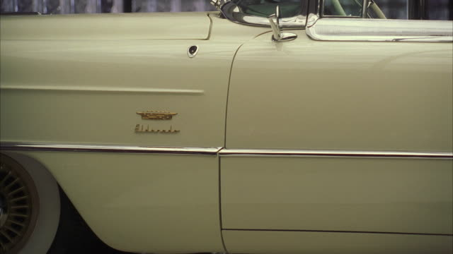 vidéos et rushes de cu white cadillac eldorado convertible rotating on turntable inside empty showroom - beige