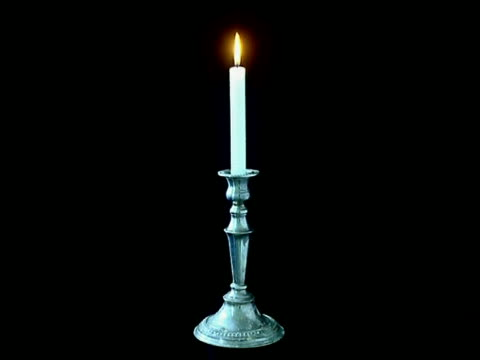 T/L - White candle in brass candlestick burns down, black background