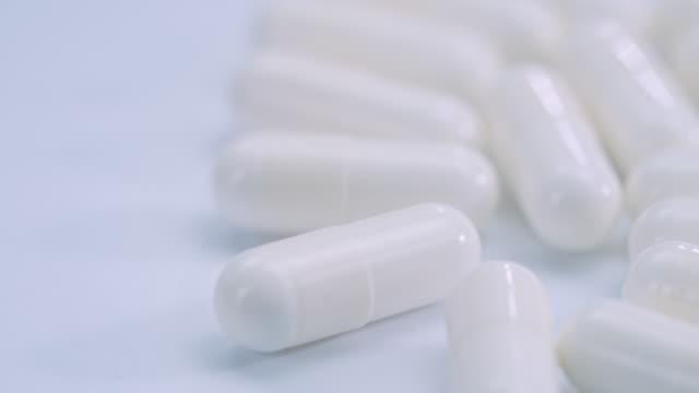 vídeos de stock e filmes b-roll de white capsule pills turning rotation on white background - vitamina a