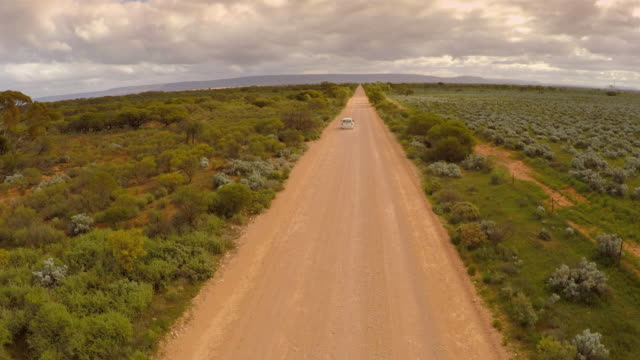 A white car drives along a dusty road in the Australian outback