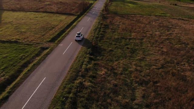 vídeos de stock, filmes e b-roll de um carro branco dirige por uma estrada rural vazia em um pôr do sol de verão dourado - idyllic