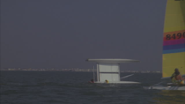 White catamaran with main sail and jib with two people with their backs to camera.