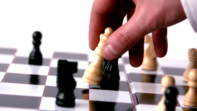 white chess piece knocking over a black one - chess piece stock videos & royalty-free footage