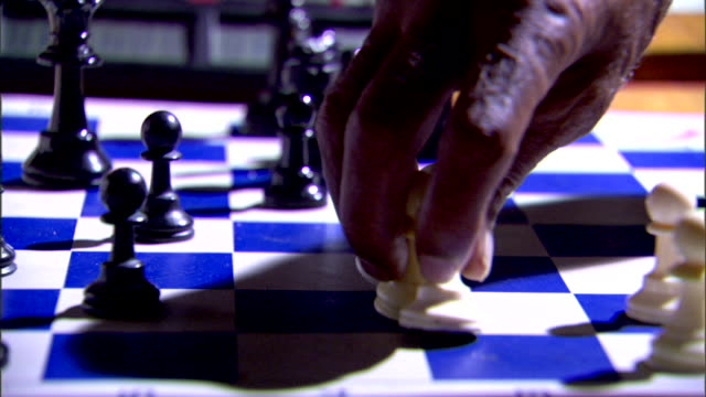 CHESS White chess pieces on board w/ pawns clustered around king OUT/IN FOCUS PAN Black male hands resetting chess board