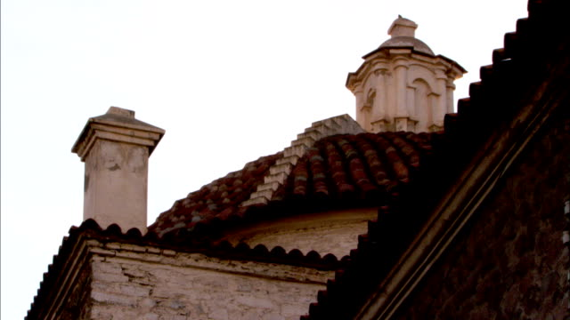 a white chimney and an ornate stone steeple rise above red-tiled, terraced rooftops. available in hd. - steeple stock videos & royalty-free footage