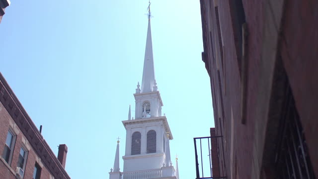 a white church spire towers above brick buildings. - spire stock videos & royalty-free footage