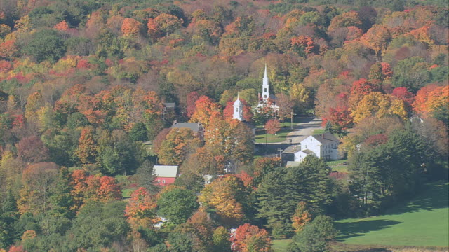 AERIAL White church steeple and small town amid fall foliage / Amherst, Massachusetts, United States