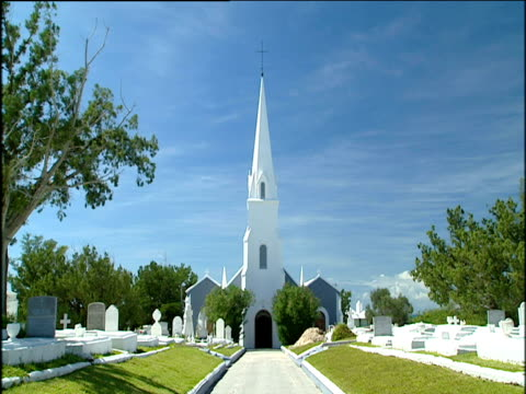 white church with white steeple reaching to the skies at end of driveway bordered on both sides by small cemetery ; bermuda - steeple stock videos & royalty-free footage