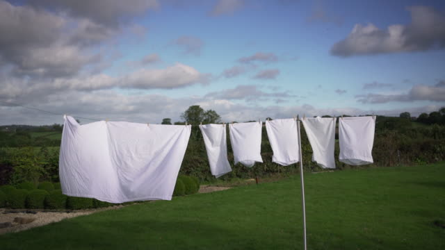 white clean bed sheets blowing in the wind - washing line stock videos & royalty-free footage
