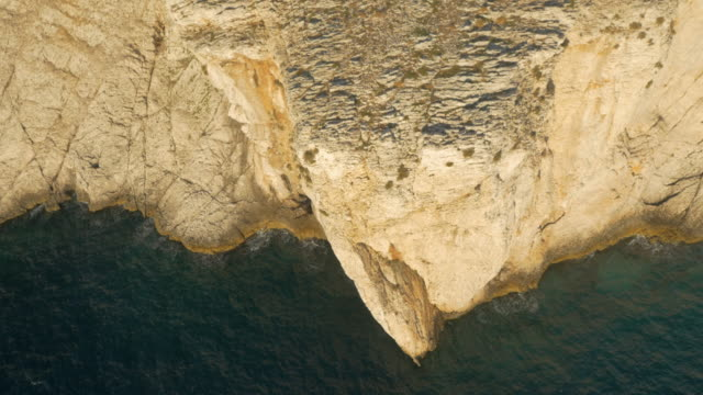 aerial white cliff along the sea in sunset - rock face stock videos & royalty-free footage