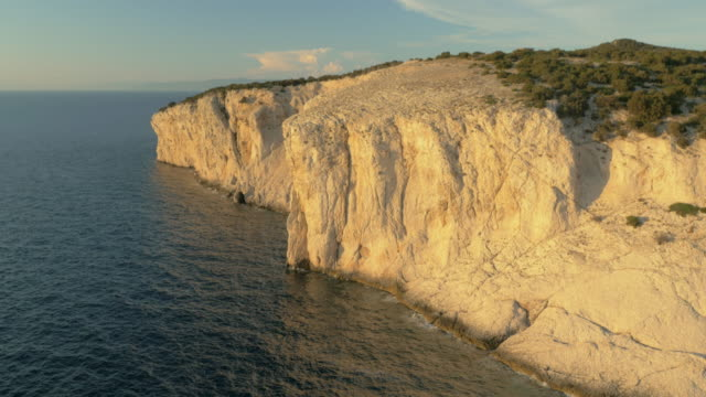 aerial white cliff raising above sea and shining in sunset - rock face stock videos and b-roll footage