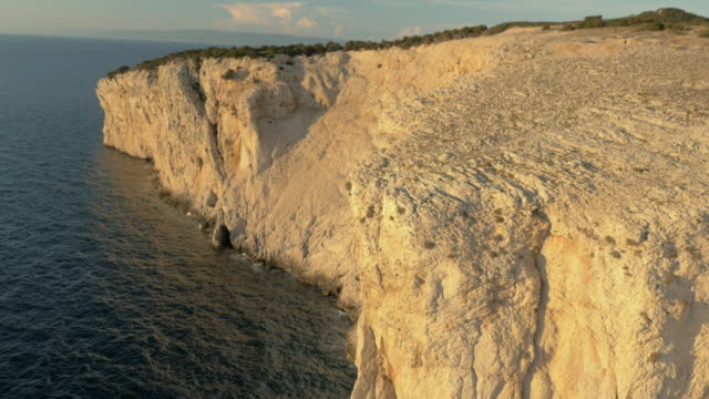 aerial white cliff shining in setting sun - rock face stock videos and b-roll footage