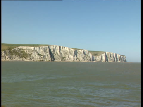 white cliffs of dover with blue sky and murky sea - 石灰岩点の映像素材/bロール
