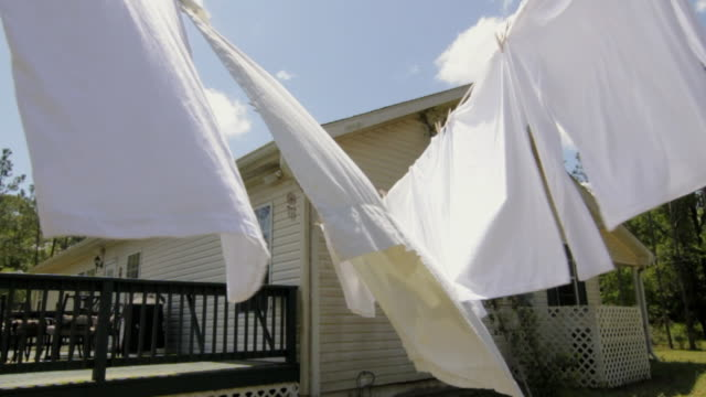 slo mo ms white clothes on clothesline in front of house / madison, florida, usa - washing line stock videos & royalty-free footage