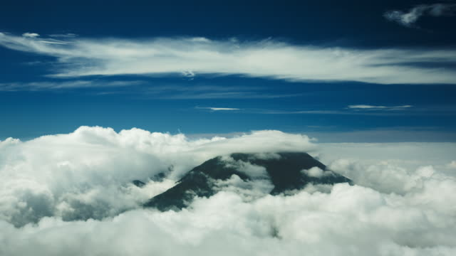 white cloud surrounds and caps dark mountaintop with blue infinity sky behind.  mount merapi, indonesia - java stock videos & royalty-free footage