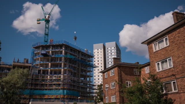 White clouds against a blue sky move rapidly pass both a high rise residential council tower block and low rise social housing with the construction of a new private development underway